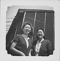 [Two women in sweaters in front of barracks, Rohwer, Arkansas]