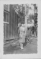[Young woman in suit near barracks and string trellises, full-length portrait, Rohwer, Arkansas]