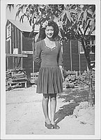 [Young woman in short dress with sweethart neckline and flower in hair, full-length portrait, Rohwer, Arkansas, October 16, 1944]