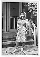 [Young woman in floral dress and headscarf in front of barracks, Rohwer, Arkansas]