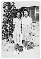[Two women standing in front of vines and barracks, full-length portrait, Rohwer, Arkansas, July 9, 1944]