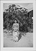 [Young woman in kimono standing in front of tree and barracks, Rohwer, Arkansas]