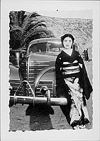 [Woman in montsuki kimono leaning on Plymouth automobile, Rohwer, Arkansas]