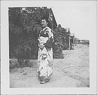 [Young woman in kimono standing in front of tree and barracks, Rohwer, Arkansas, September 13, 1944]