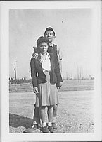[Couple standing in open graveled area, Rohwer, Arkansas]