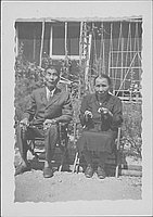 [Older couple holding Buddhist religious articles, seated portrait, Rohwer, Arkansas, July 7, 1944]