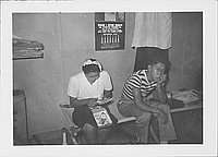 [Young man and woman sit on cot under calendar, Rohwer, Arkansas]