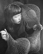 Ruth Asawa holding a form-within-form sculpture, 1952.